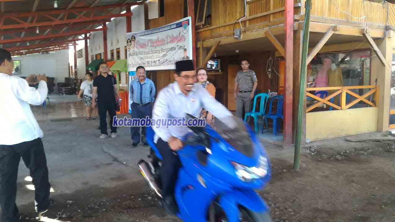 Bupati Sehan Lanjar, saat mengendarai motor Ninja menuju lokasi Apel Perdana Desa Tutuyan Dua tempat ribuan PNS menunggu. (dok : kotamobagu post )