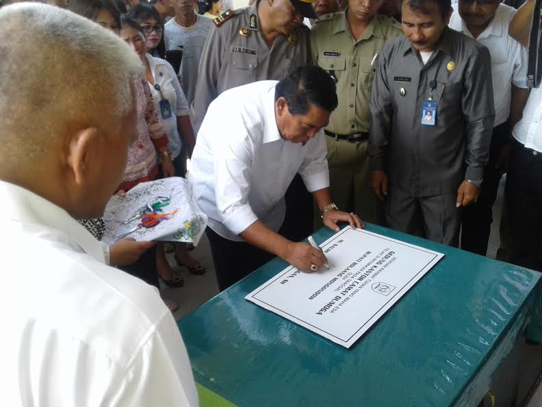 Bupati Bolmong Salihi Mokodongan tampak melakukan penandatanganan prasasti peresmian gedung baru Kantor Camat Dumoga di Desa Pusian.
