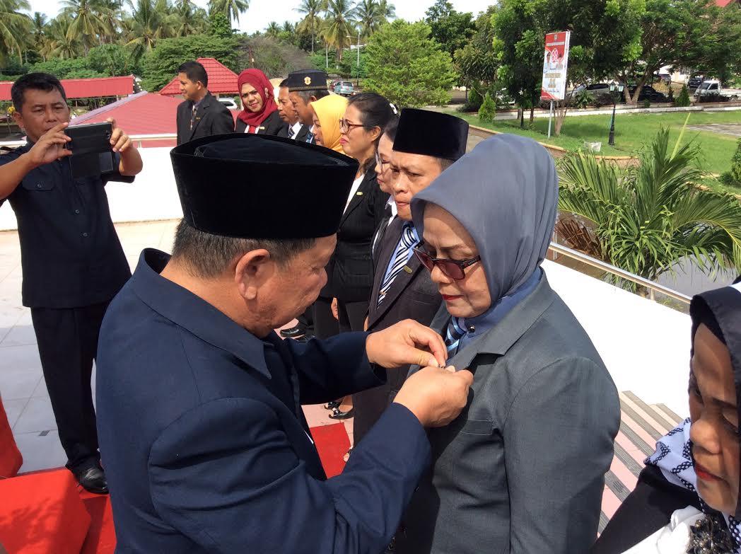 Bupati Bolmong Adrianus Watung menyematkan pin  tanda penghargaan kepada salah satu ASN Bolmong