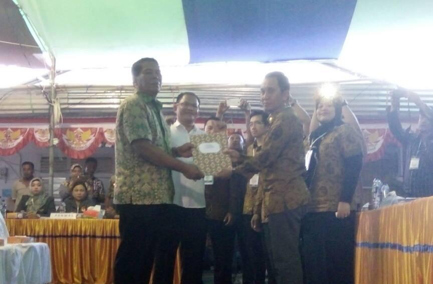 Ketua KPU Bolmong Fahmi Gobel saat menyerahkan dokumen penetapan pasangan calon kepada salah satu pasangan calon (dok : KPU BM)
