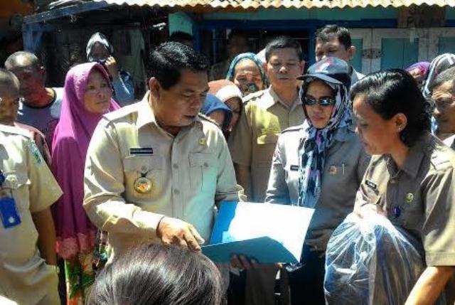 Bupati Bolmong Salihi Mokodongan saat menyerahkan bantuan kepada korban kebakaran. (Foto : Humas Bolmong)