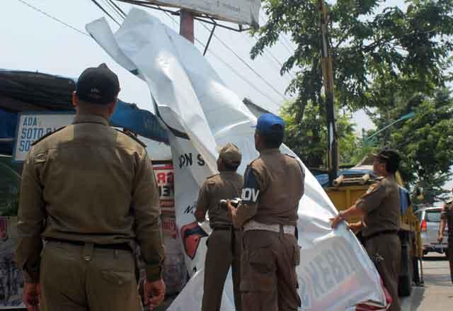 Anggota Satuan Polisi-Pamong Praja Kota Kotamobagu dalam operasi penertiban reklame ilegal (dok :ttn)